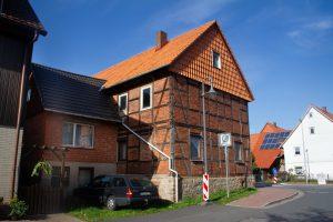Einfamilienhaus in 37520 Osterode am Harz mit Anbau und Scheune - Giebelansicht und PKW-Stellplatz